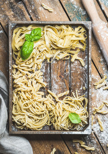 Various uncooked Italian pasta in wooden tray over rustic background