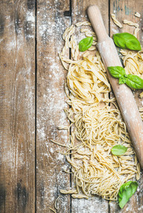 Various homemade fresh uncooked Italian pasta with flour  basil