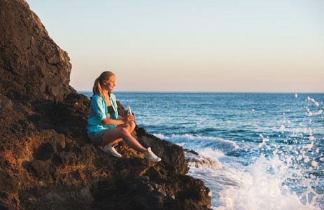 Young blond woman tourist with glass bottle of lemonade sittig on rocks by the sea at sunset Alanya Mediterranean region Turkey