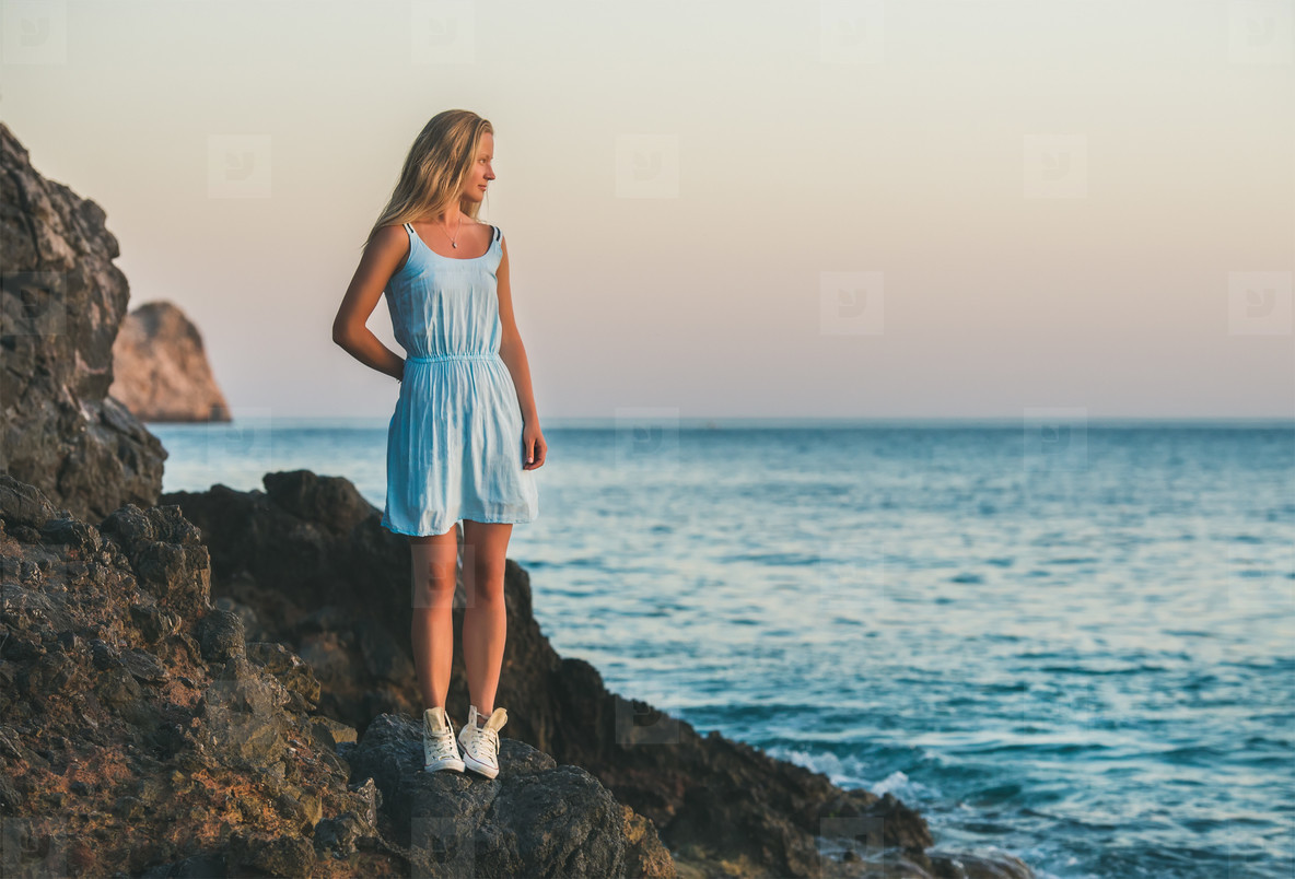 Young blond woman standing on rocks by sea  Alanya  Turkey