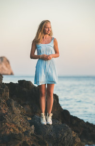 Young blond woman standing on rocks by the sea