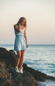 Young blond woman standing near sea and looking down Turkey