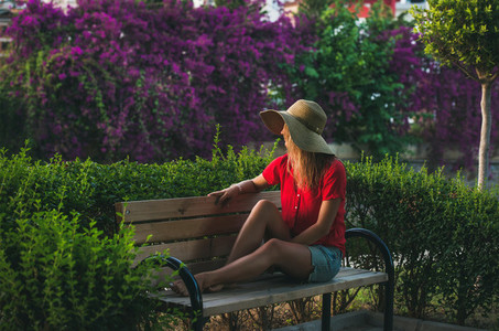 Young woman sitting on bench and looking aside  Alanya  Turkey