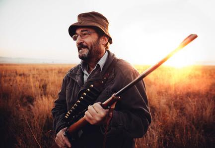 Hunter on field in sunrise