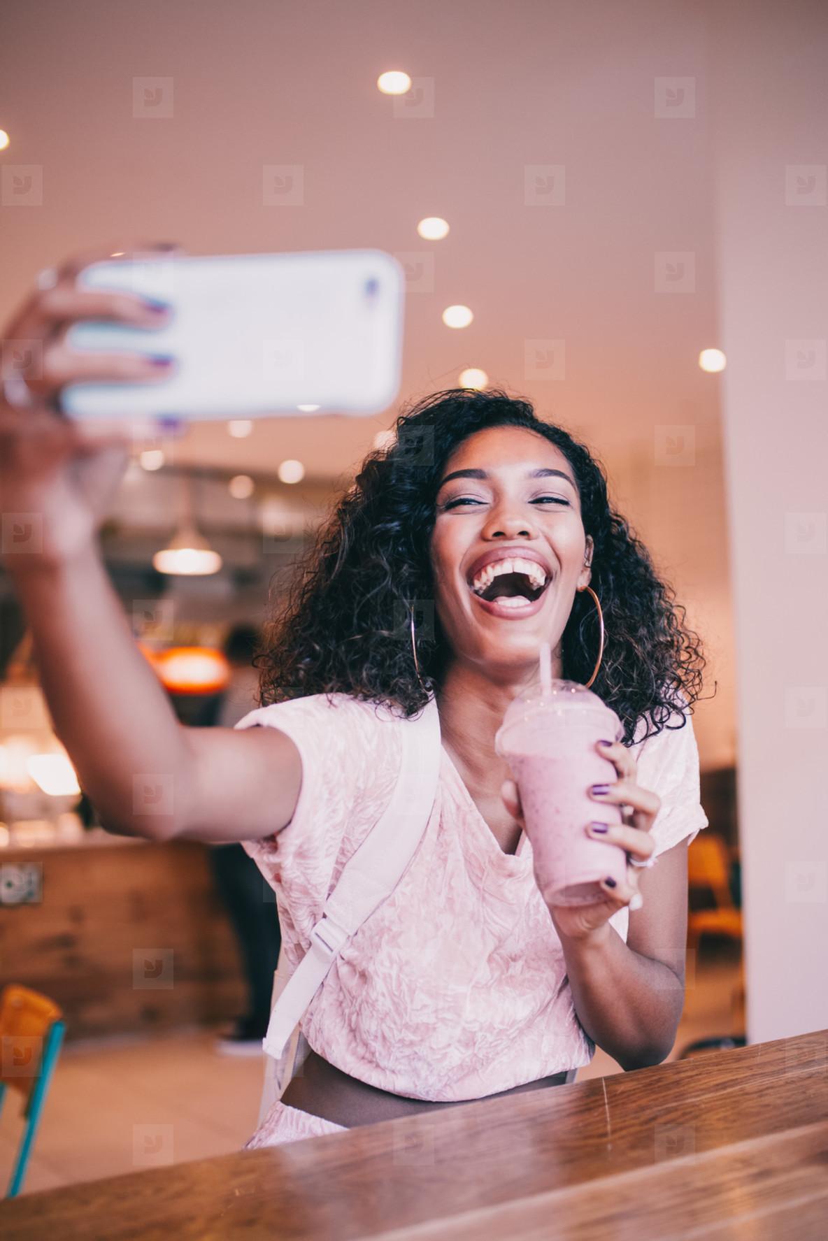 woman taking selfie in cafe