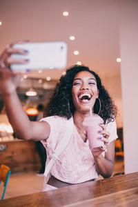 woman taking selfie in cafe
