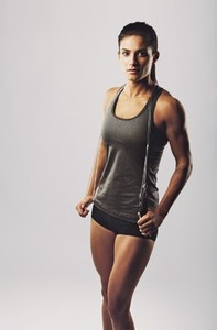 Female with muscular body posing with jump rope