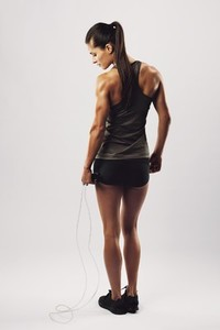 Fit and muscular woman with jumping rope