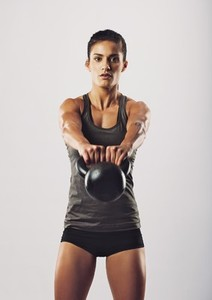 Young fit woman performing kettlebell swing exercise