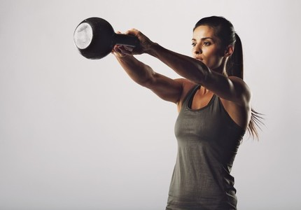 Attractive female doing kettle bell exercise