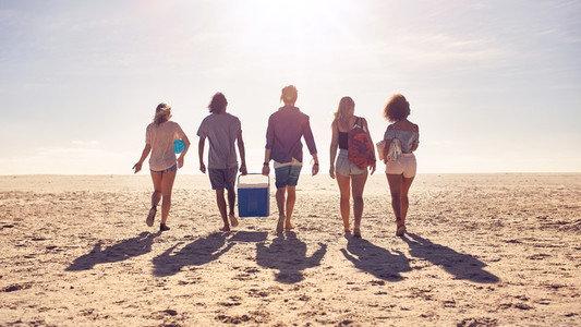 Friends walking on the beach carrying a cooler box