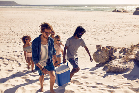 Group of friends carrying cooler to party on beach
