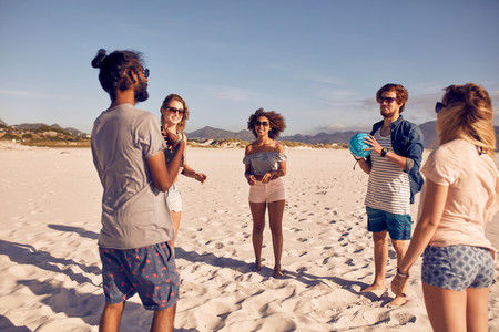Group of friends on the beach playing with ball