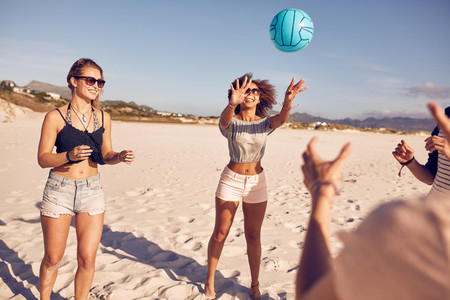 Group of friends on the beach playing volleyball