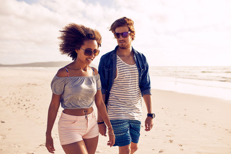 Young couple strolling on the shoreline