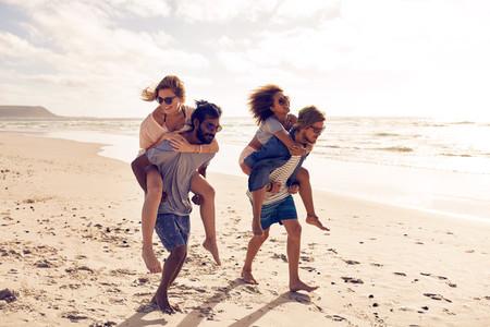 Friends piggyback along the beach