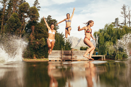 Girls jumping into a wilderness lake