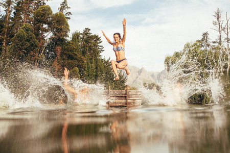 Women jumping into a lake from jetty
