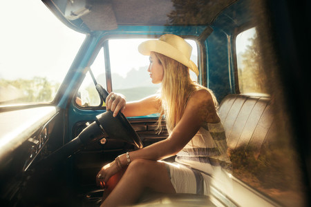 Young woman sitting on driving seat of a car