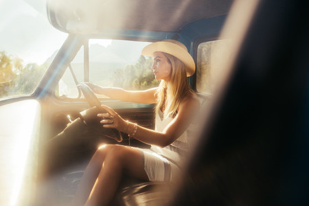 Beautiful young woman driving a car on sunny day