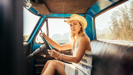 Attractive young woman sitting in a car