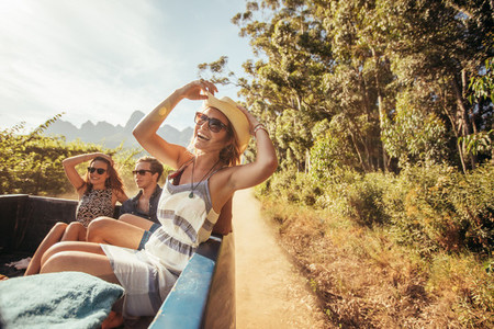 Cheerful young woman with friends in the back of a pickup truck