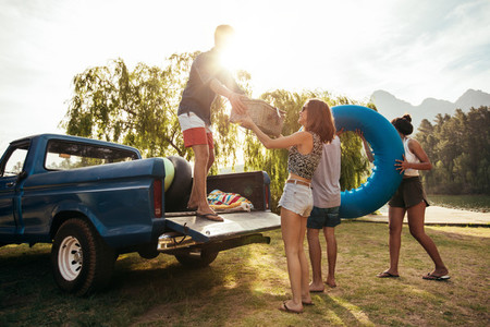 Young friends unloading pickup truck on camping trip