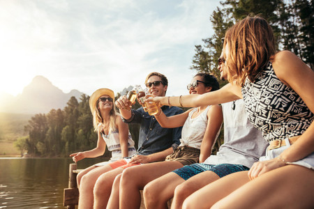 Young people toasting beers on a jetty