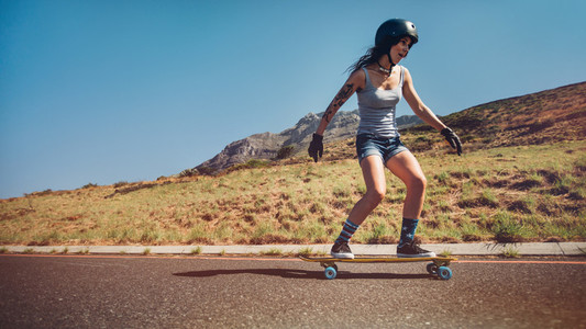 Young woman skateboarding down a road