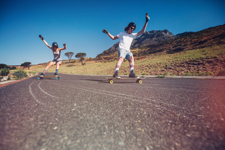 Young couple skateboarding on the road