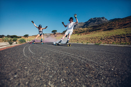 Young people skateboarding with smoke bomb on the road