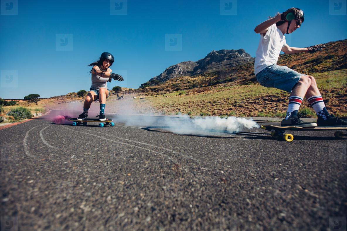 Teenagers longboarding on open road