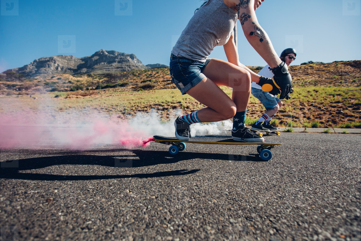 Man and woman longboarding down the road