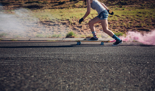Young woman longboarding down the road