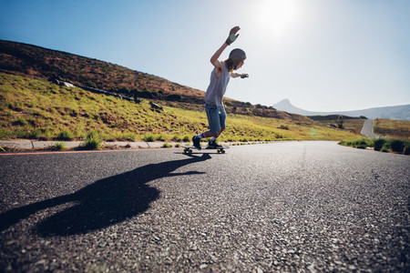 Young man skateboarding down the road