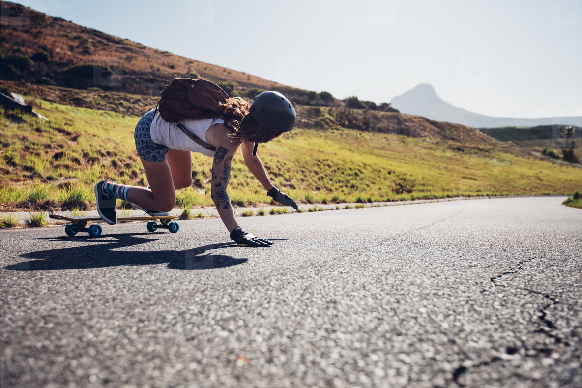 Young woman practicing skateboarding on rural roads