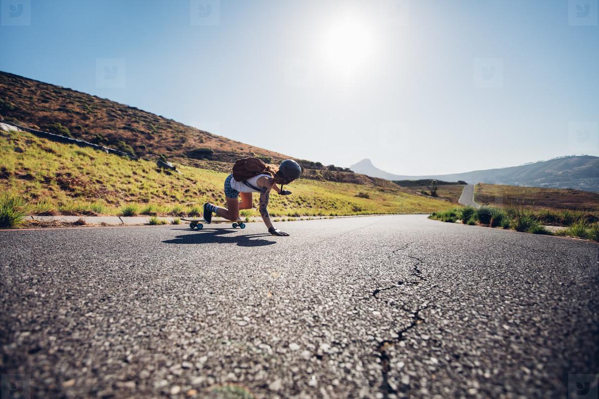 Female skater practicing skateboarding on rural roads