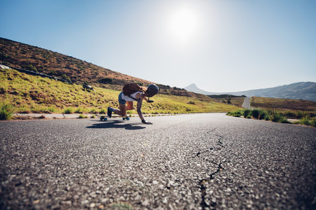 Female skater practicing skateboarding on rural roads