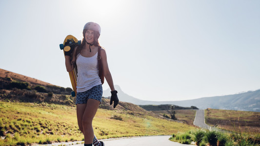 Woman walking with a longboard on countryside road