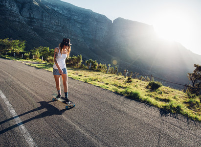 Young woman skating outdoors on rural road