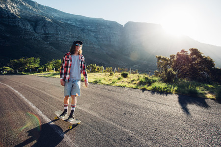Young man longboarding outdoors on rural road