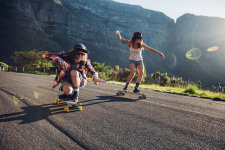 Happy young friends having fun with skateboard