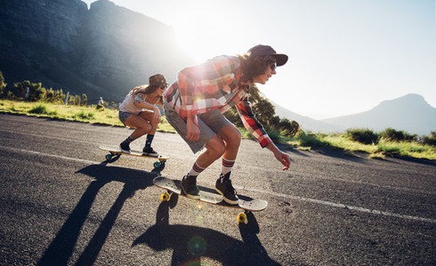 Young friends longboarding down the road