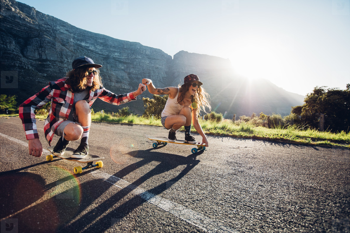 Couple having fun with skateboard on the road