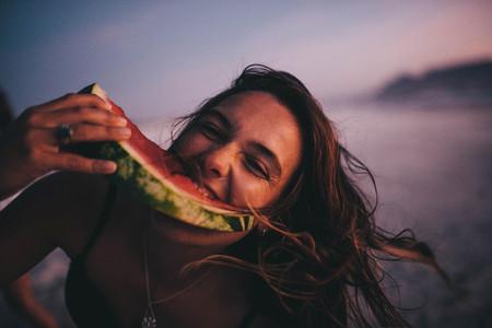 Woman eating watermelon on beach