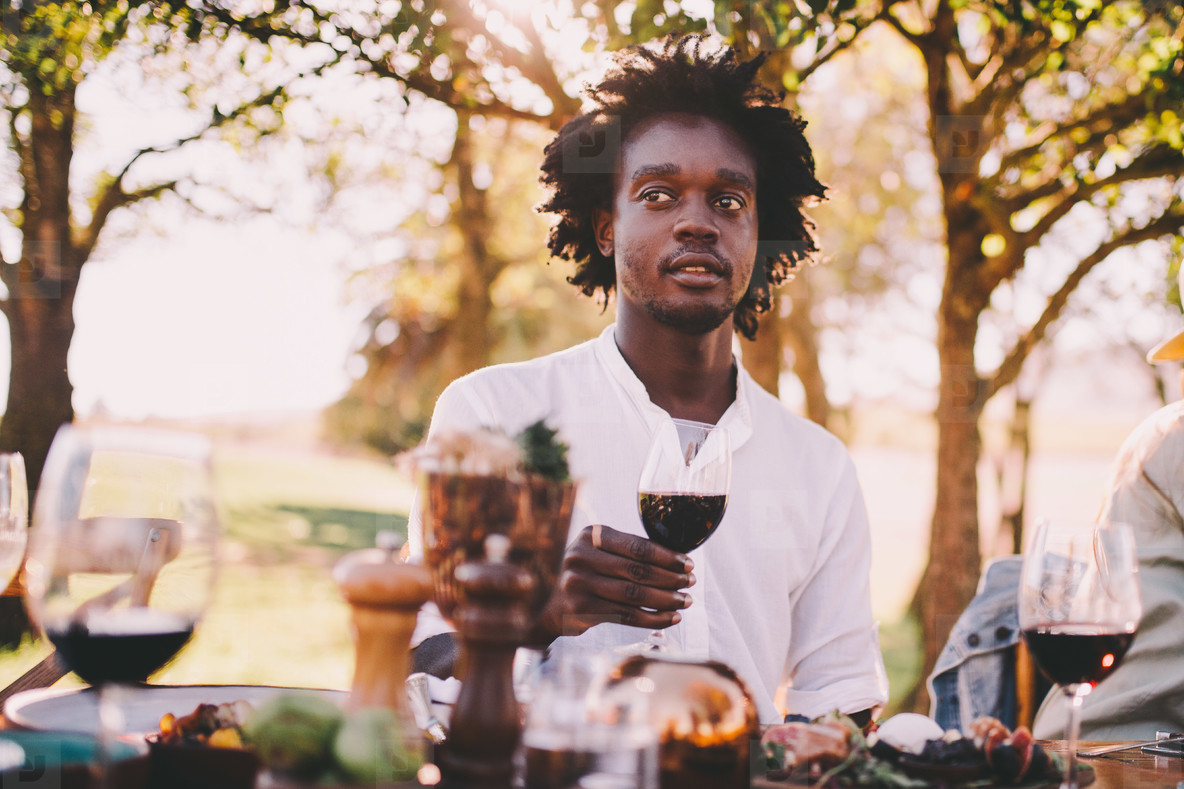 Afro American man enjoying wine at lunch party