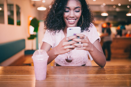 Smiling woman typing message on smartphone in Bar