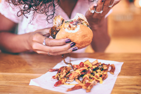 Close up of woman eating fries and Hamburger