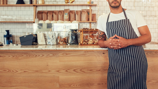 Man standing at a coffee shop counter with an apron