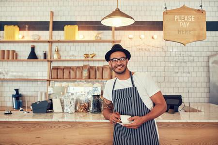 Barista standing at bar counter and smiling at camera